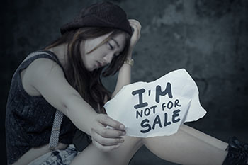Sad woman holds sign that says, 'I'M NOT FOR SALE.'